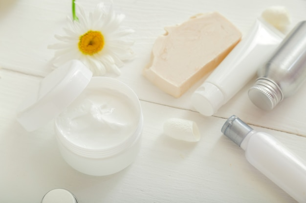 카모마일 꽃이 든 흰색 항아리에 모이스처 라이저 스킨 크림은 튜브와 병에 흰색 스킨 케어 제품 비누를 설정합니다. 모이스처 라이저 스킨 크림, 흰색 배경에 로션에 대한 모형 흰색 플라스틱 항아리.