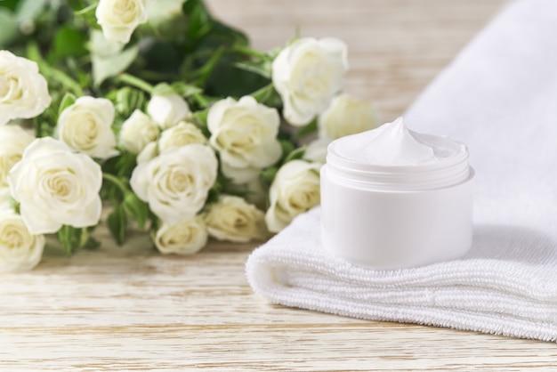 나무 테이블에 수건이 있는 흰색 플라스틱 항아리에 민감한 피부 스킨케어 제품을 위한 보습 크림. 피부 정화 화장품 고급 크림 또는 비타민 스파 로션.