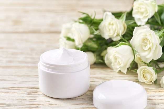 흰 장미를 배경으로 민감한 피부, 스파 화장품, 천연 청정 스킨케어 제품을 위한 보습 크림.