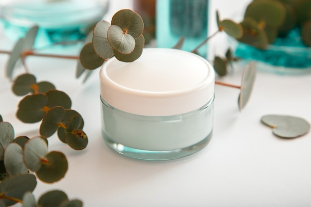 Moisturizing cream in glass jar with eucalyptus leaves. set of eucalyptus skin care cosmetics in white mockup packaging on white background. natural skincare cosmetics or medical eucalyptus ointment.