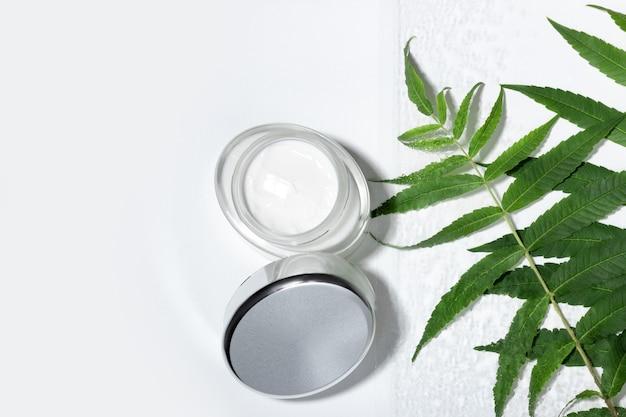 保湿効果のある顔とまぶたのクリームに天然抽出物を配合。葉が付いているガラス化粧品の瓶。天然化粧品