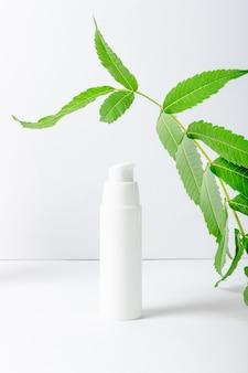 保湿効果のある顔とまぶたのクリームに天然抽出物を配合。新鮮なハーブと白い化粧品チューブ
