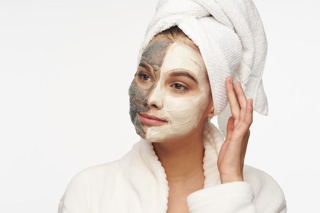 보습 페이스 마스크 스크럽 화장품은 피부를 깨끗하게합니다. 수건으로 흰 코트를 입은 여성