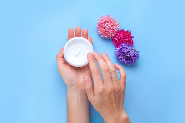 Moisturizing hand cream and flowers. hand care. elimination of dry skin of the hands.