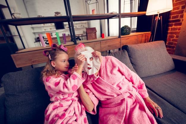 保湿マスク。おばあちゃんの顔に保湿マスクをつけながら巻き込まれた気持ちの可愛い女の子を気遣う