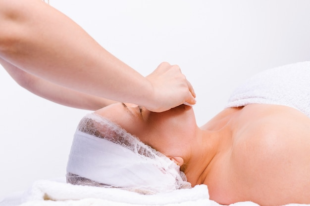 Moisturizing and relaxing massage for an older woman and the hands of a master on a white background