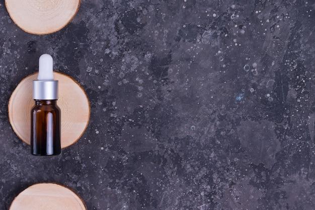 회색 테이블에 나무 스탠드에 유리 병에 주름과 여드름에 대한 얼굴 피부에 대한 콜라겐과 달팽이의 점액이있는 보습 세럼