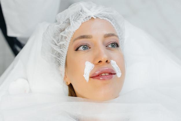 若い女性のための美容処置中の唇の保湿