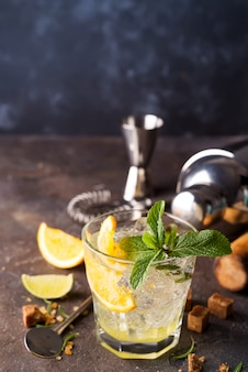 Mojito or caipirinha cocktail. brown sugar and an empty glass on stone