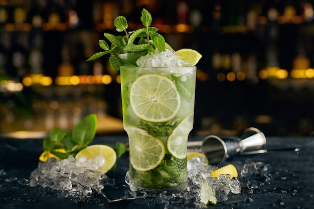 Mojito cocktail, against the surface of bottles, on the bar, with bar attributes
