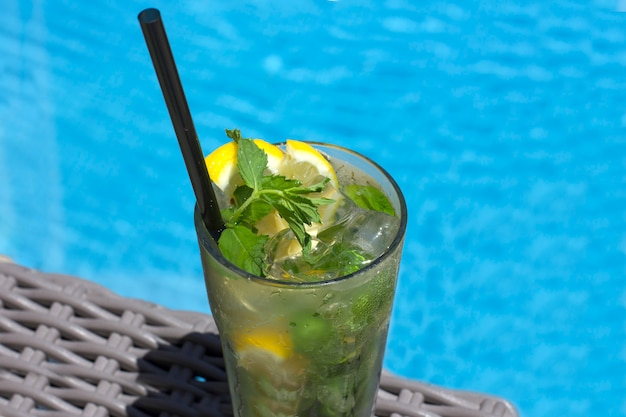 Mojito cocktail in glass on the background of the pool