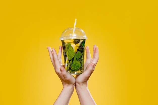 Коктейль мохито в пластиковом стакане с тубусом на желтом фоне. летом прохладительный напиток на вынос. место для текста.