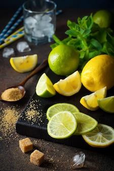 Ингредиенты коктейля мохито, свежая мята, лайм, лимон, сахар, лед на темноте.