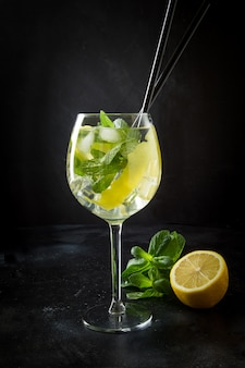 Mojito cocktail or lemonade with mint in glass on black close up summer drink