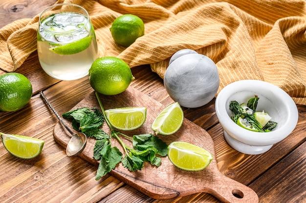 Приготовление коктейлей мохито. ингредиенты мята, лайм, лед и барная посуда. деревянный фон. вид сверху.