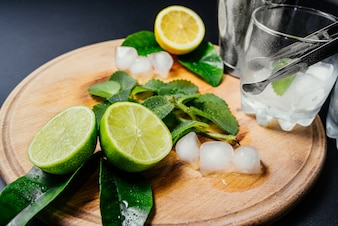 Mojito cocktail making. Mint, lime, lemon ice ingredients and bar utensils.