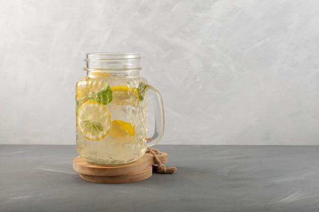 モヒートカクテルガラスのカクテルジャーにレモンライムとミントを入れたさわやかな夏の飲み物。