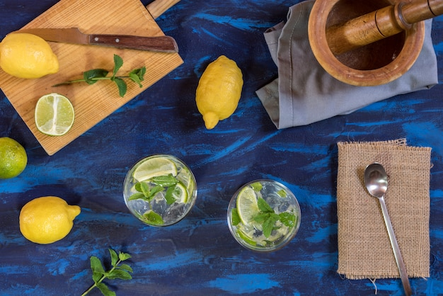 Mojito cocktail with its ingredients on a blue table