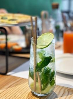 Коктейль мохито с лаймом и мятой в стакане на деревянном столе