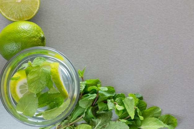 Mojito cocktail with lime and mint in glass on a grey wall