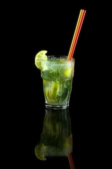 Коктейль мохито с лаймом, листьями мяты и кубиками льда, освежающий летний напиток с трубочкой, на черном фоне