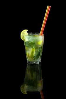 Mojito cocktail with lime, mint leaves and ice cubes, refreshing summer drink with a straw, over black background