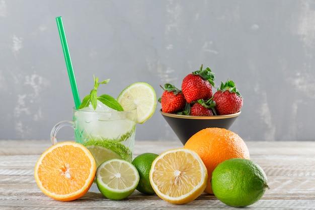 Коктейль мохито с лаймы, солома, апельсины, лимон, клубника, мята в чашку на деревянных и штукатурка, вид сбоку.