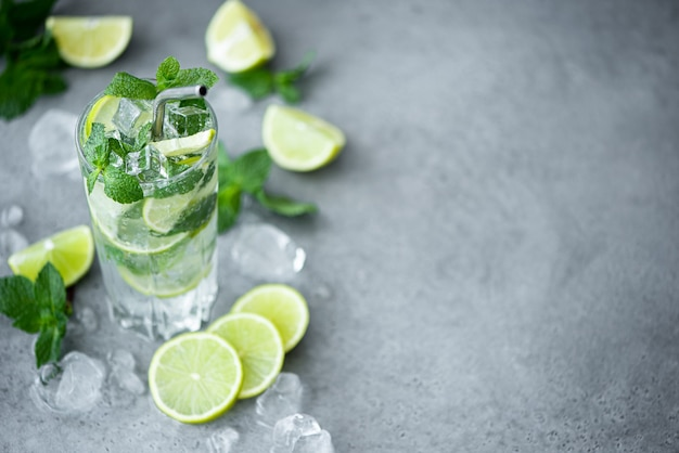 Mojito cocktail with mint, lime and ice in a tall on a grey background