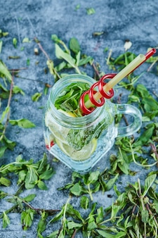 Mojito cocktail with slices of lime and mint on blue table with fresh mint leaves