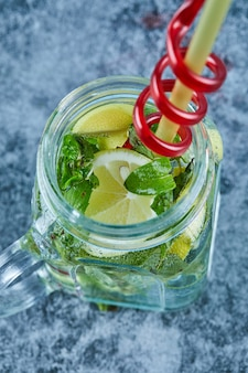 Mojito cocktail with slices of lime and mint on blue table