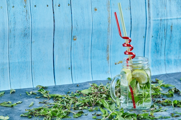 新鮮なミントの葉と青いテーブルの上にライムとミントのスライスとモヒートカクテル