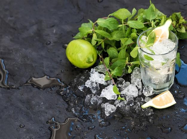 モヒート調理セット。黒いスレート石の背景に新鮮なミント、ライム、砕いた氷、カクテルグラスの束