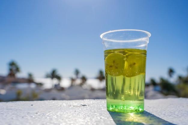 晴れた日、エジプトの熱帯のビーチの背景にプラスチック製のコップでモヒートを飲む