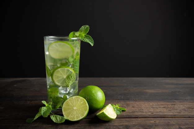 Mojito drink with lime, lemon and mint on wood table.