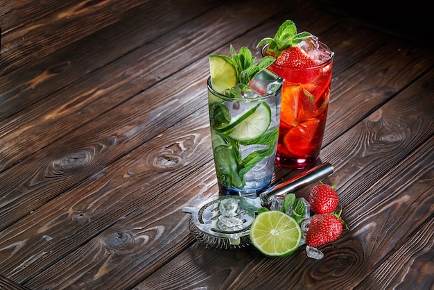 Mojito drinks with lime, strawberry and mint in glass with ice cubes on wooden background