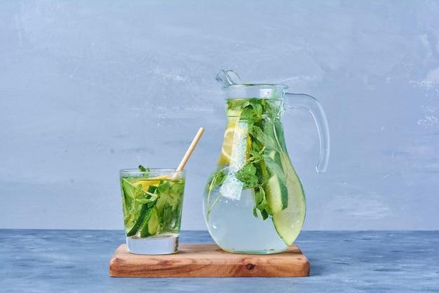 Мохито с лимоном и мятой на деревянной доске на синем