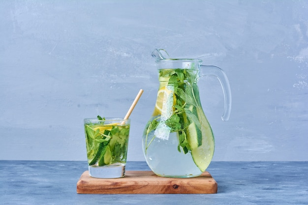 Mojito with lemon and mint on a wooden board on blue