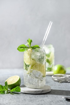 Mojito with lime mint and ice cube on gray background