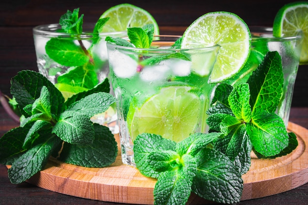 Mojito with mint and lime in a glass and a jug on the round boar