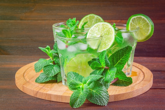 Mojito with mint and lime in a glass and a jug on the round board. brown wood background.