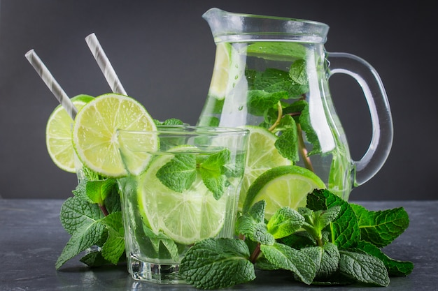 Mojito with mint and lime in a glass and a jug with tubes. grey marble background.