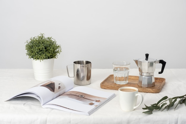 Moka and glass of water on the wooden tray, plant in pot, magazi