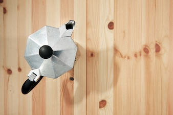 Moka pot coffee maker from top view on wooden table with soft shutter