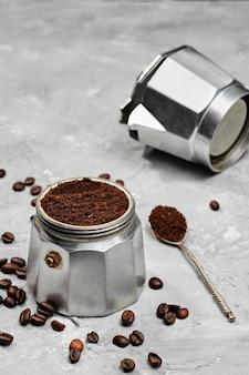 挽いたコーヒー、クローズアップ、セレクティブフォーカス、グレーのミニマルなニュートラルな背景で満たされたモカポット。間欠泉コーヒーメーカーでイタリアンコーヒーを準備する