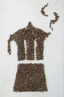 Moka pot made of freshly roasted coffee beans on a marble background with tea spoon. coffee pattern.
