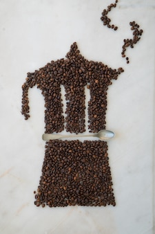 大理石の背景に淹れたてのコーヒー豆とティースプーンで作ったモカポット。コーヒーパターン。