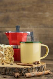 Желтая чашка олова горячего кофе с итальянским кофейником (moka) и торт на деревянном столе.