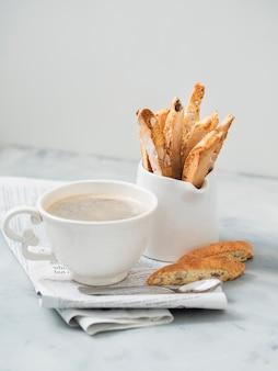 ビスコッティ - 一杯のコーヒーとmokaコーヒーポットが新聞に並ぶ伝統的なイタリアのアーモンドデザート。