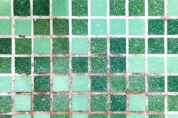 욕실의 세라믹 타일 사이의 이음매에 곰팡이. 청소하기 전에 녹색 모자이크 타일의 흰색 이음새에 있는 오래된 검은 독성 곰팡이 흙. 샤워실 벽에 더러운 곰팡이나 곰팡이