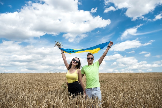Molda happy couple with flag of ukraine in wheat field. lifestyle